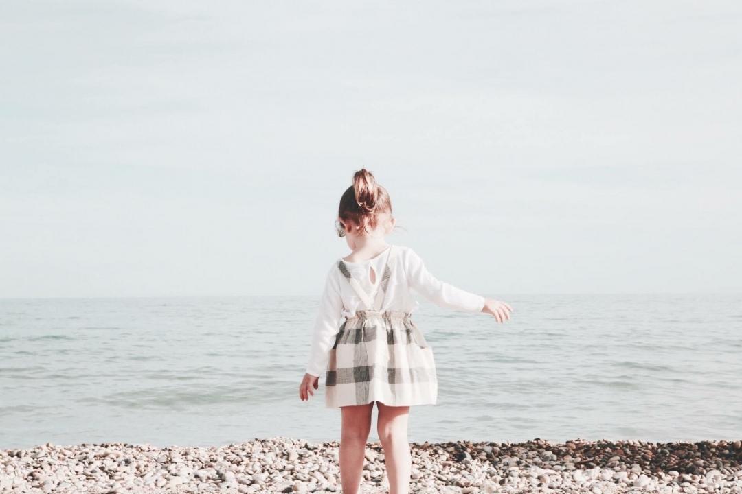 Child Walking Toward Ocean